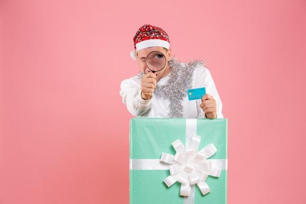 분홍색 벽에 돋보기와 은행 카드를 확인하는 젊은 남자의 전면보기