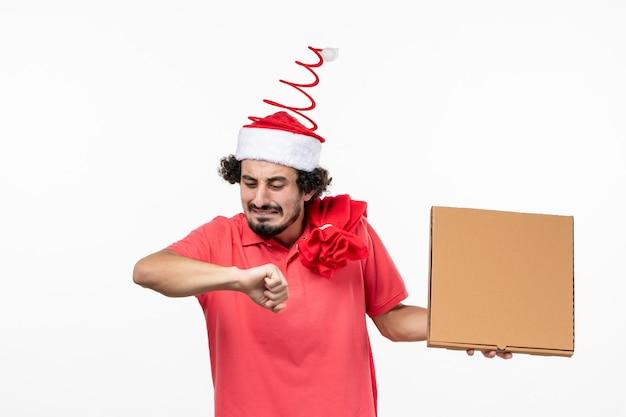白い壁に配達フードボックスで時間をチェックする若い男の正面図