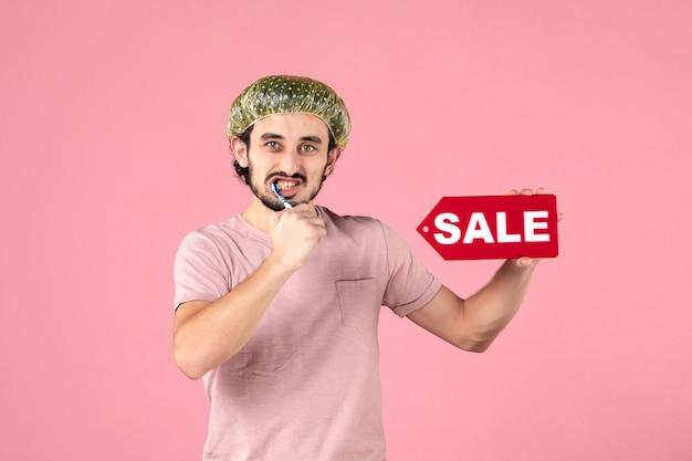 彼の歯を掃除し、ピンクの壁に販売バナーを保持している若い男の正面図