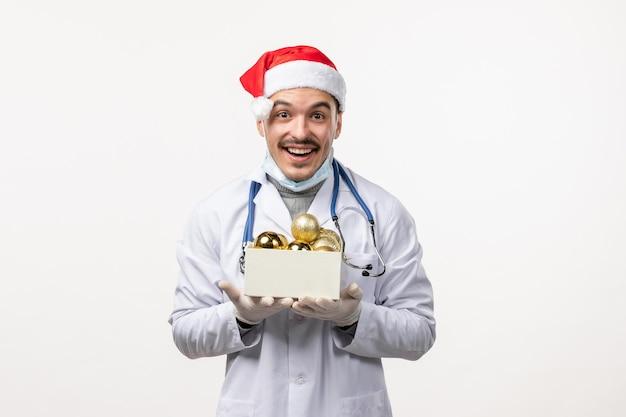 흰 벽에 장난감을 들고 있는 젊은 남자 의사의 전면 모습