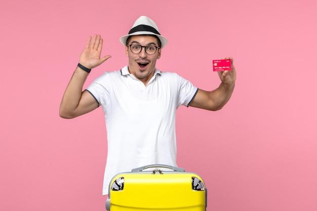 Вид спереди молодого человека, эмоционально держащего банковскую карту в отпуске на розовой стене