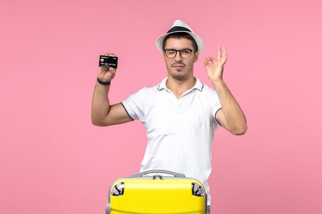 Вид спереди молодого человека, эмоционально держащего черную банковскую карту на розовой стене