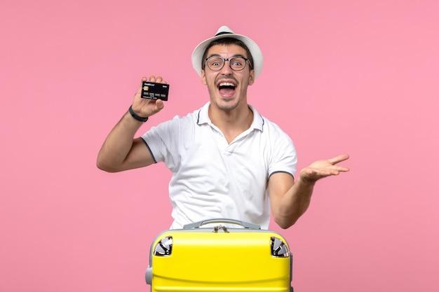 분홍색 벽에 검은색 은행 카드를 감정적으로 들고 있는 청년의 전면 모습