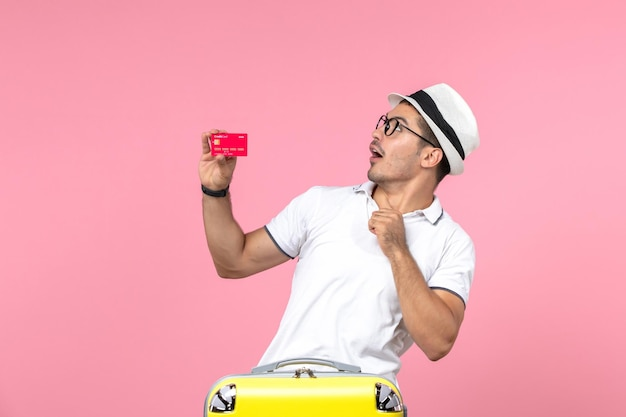 Вид спереди молодого человека, эмоционально держащего красную банковскую карту в отпуске на розовой стене