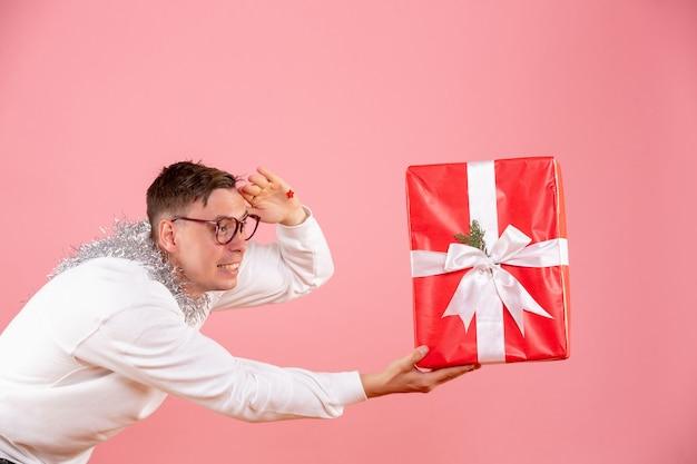 Вид спереди молодого человека, дающего кому-то рождественский подарок на розовой стене