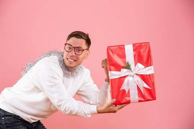 분홍색 벽에 누군가에게 크리스마스 선물을주는 젊은 남자의 전면보기