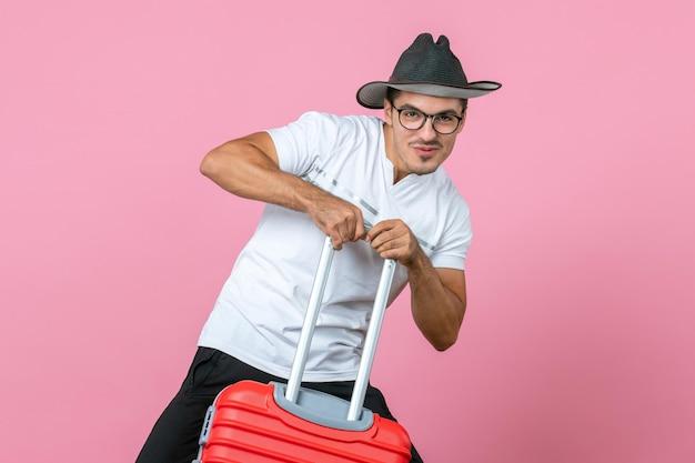 휴가를 가고 분홍색 벽에 빨간 가방을 들고 있는 젊은 남자의 전면 보기