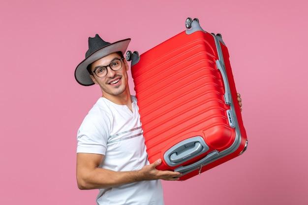 Вид спереди молодого человека, отправляющегося в отпуск и держащего красную сумку на розовой стене