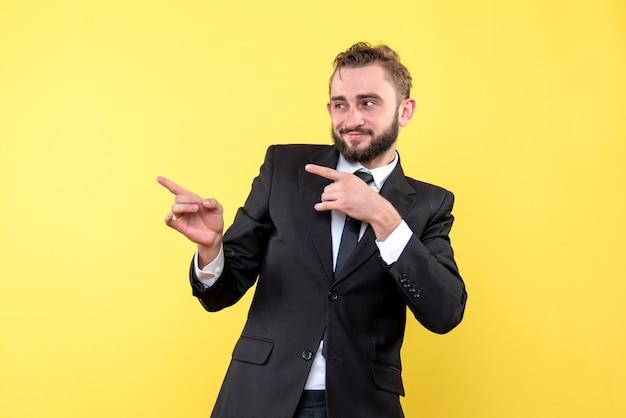 黄色の脇に指を指している若い男の幸せな実業家の正面図