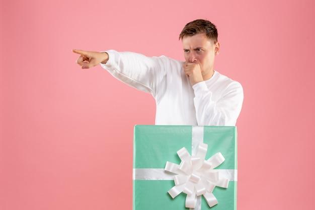 ピンクの壁にプレゼントの中に隠れている若い男の正面図