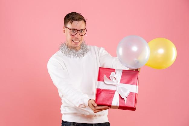 風船を持ってピンクの壁に存在する若い男の正面図