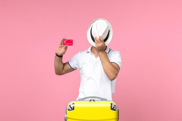 분홍색 벽에 은행 카드와 모자를 들고 있는 청년의 전면 모습