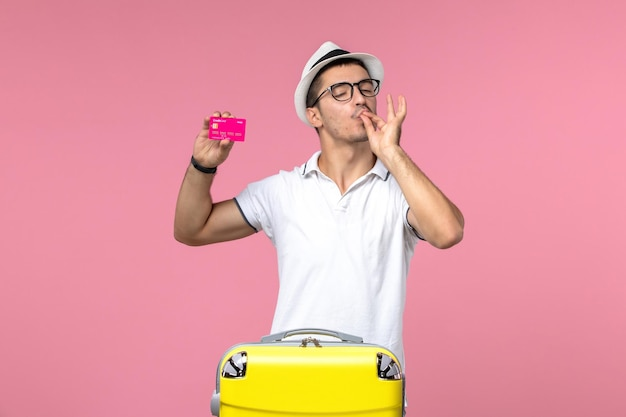 ピンクの壁に銀行カードを保持している若い男の正面図
