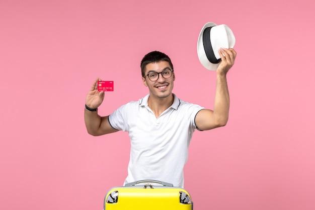 Вид спереди молодого человека, держащего банковскую карту на розовой стене