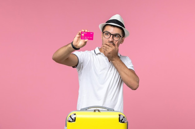 분홍색 벽에 은행 카드를 들고 있는 청년의 전면 모습