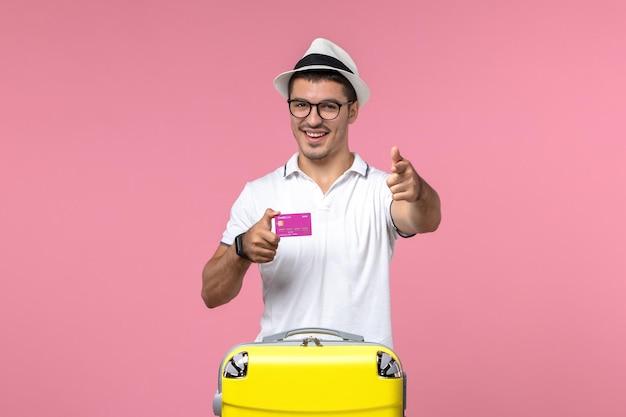 Вид спереди молодого человека, держащего банковскую карту на летних каникулах на розовой стене