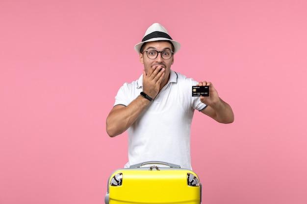 분홍색 벽에 여름 방학에 은행 카드를 들고 있는 젊은 남자의 전면 보기