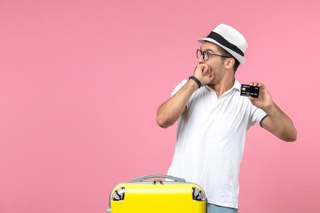 ピンクの壁に夏休みに銀行カードを保持している若い男の正面図