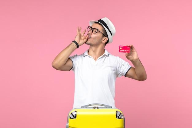 분홍색 벽에 휴가를 위해 은행 카드를 들고 있는 청년의 전면 모습