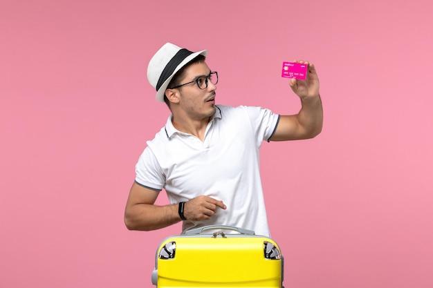 연분홍색 벽에 휴가 중 은행 카드를 들고 있는 청년의 전면 모습