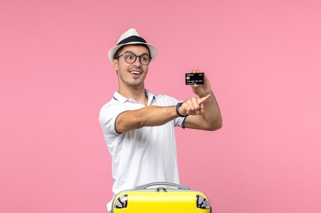 분홍색 벽을 가리키는 휴가에 은행 카드를 들고 있는 젊은 남자의 전면