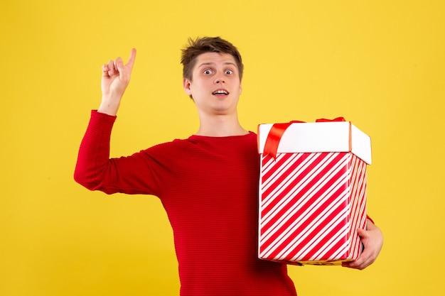 노란색 벽에 큰 크리스마스 선물을 들고 젊은 남자의 전면보기