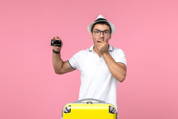 분홍색 벽에 검은색 은행 카드를 들고 있는 청년의 전면 모습
