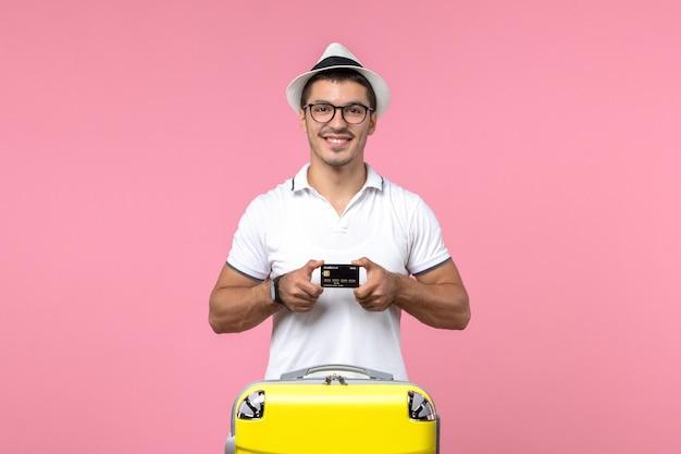 분홍색 벽에 감정이 담긴 검은색 은행 카드를 들고 있는 청년의 전면 모습