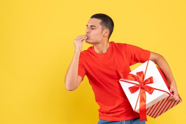 Вид спереди молодого человека, держащего рождественский подарок на желтой стене
