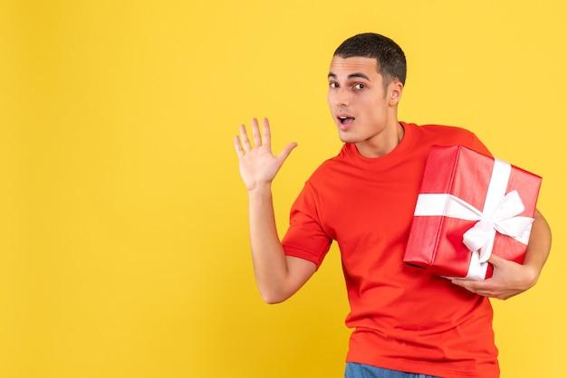 黄色の壁に手を振ってクリスマスプレゼントを保持している若い男の正面図