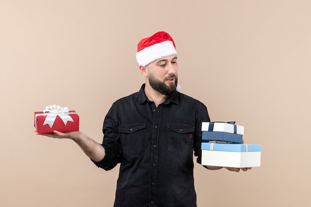 분홍색 벽에 크리스마스 선물을 들고 젊은 남자의 전면보기