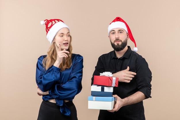Вид спереди молодого человека, держащего рождественские подарки с женщиной на розовой стене