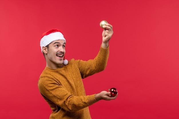 赤い壁にクリスマスツリーのおもちゃを保持している若い男の正面図