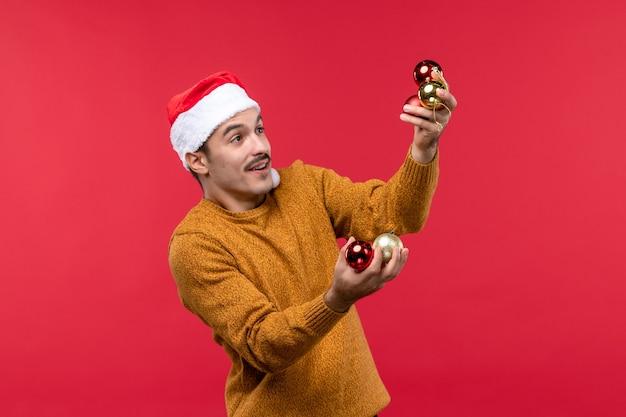 빨간 벽에 크리스마스 트리 장난감을 들고 젊은 남자의 전면보기