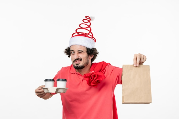 Вид спереди молодого человека, держащего доставку кофе на белой стене