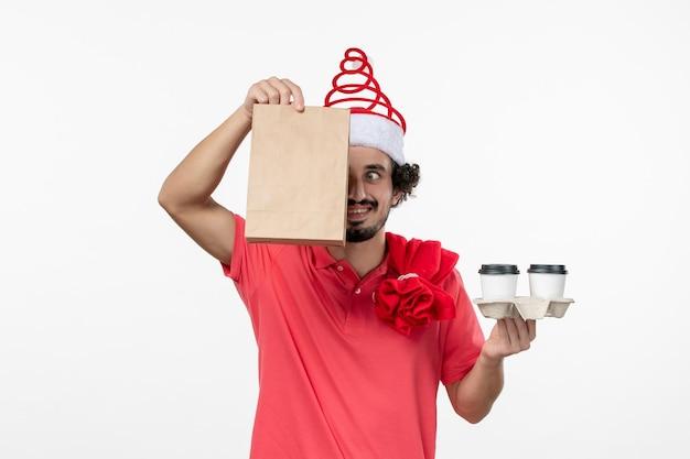 흰 벽에 배달 커피를 들고 있는 젊은 남자의 전면 모습