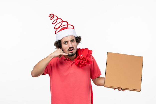 白い壁に配達フードボックスを保持している若い男の正面図