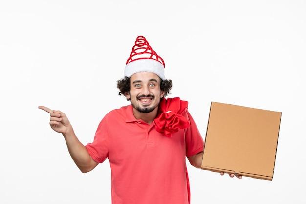 흰 벽에 배달 음식 상자를 들고 있는 젊은 남자의 전면 모습