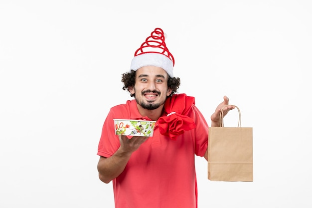 흰 벽에 배달 음식을 들고 있는 젊은 남자의 전면 모습