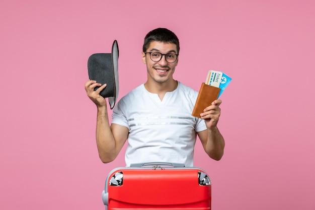 ピンクの壁に帽子と飛行機のチケットを保持している若い男の正面図