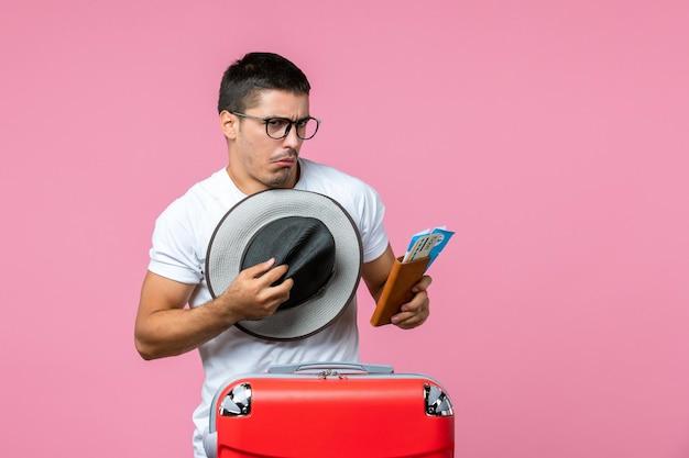 Вид спереди молодого человека, держащего шляпу и билеты на самолет на светло-розовой стене