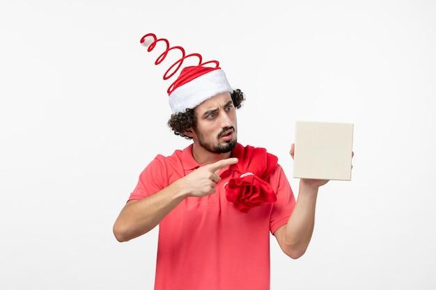 白い壁に休日のプレゼントを保持している若い男の正面図
