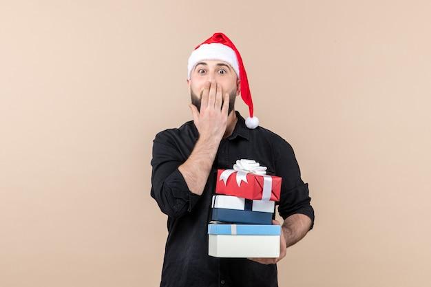 ピンクの壁に休日のプレゼントを保持している若い男の正面図