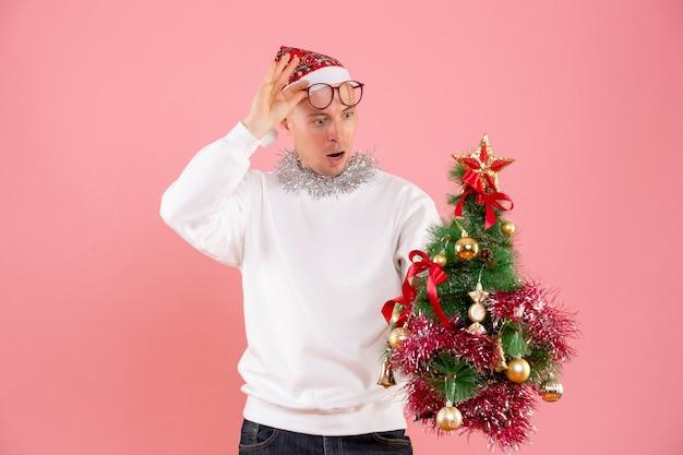 ピンクの壁に小さなクリスマスツリーを保持している若い男の正面図