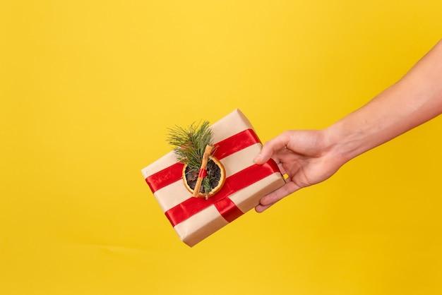 黄色の壁に存在する小さなクリスマスを保持している若い男の正面図