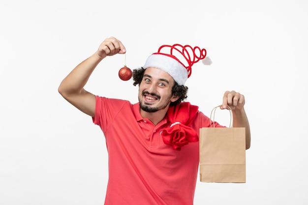 흰 벽에 선물을 들고 있는 젊은 남자의 전면 모습