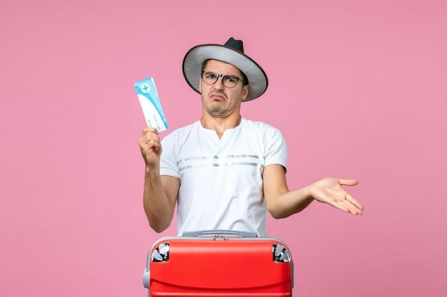 Вид спереди молодого человека, держащего билет на самолет в отпуск на розовой стене