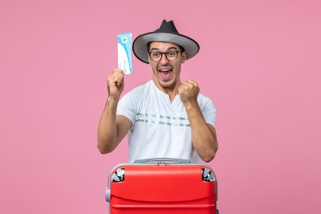 薄ピンクの壁に休暇の飛行機のチケットを保持している若い男の正面図