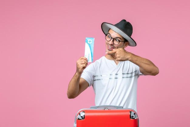 ピンクの壁に休暇の飛行機のチケットを保持している若い男の正面図