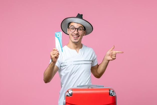Вид спереди молодого человека, держащего билет на самолет в отпуск на светло-розовой стене